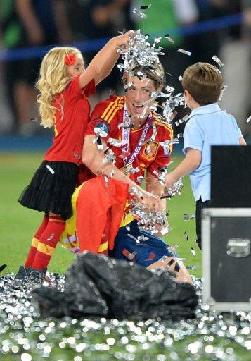 Spanish forward Fernando Torres plays with children after the match