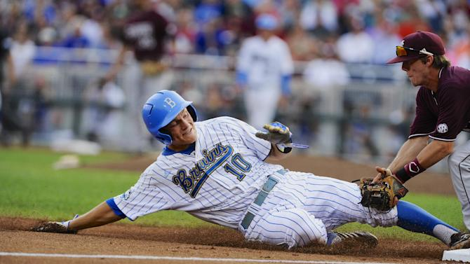 UCLA's Pat Valaika is tagged out at third base by Mississippi State third baseman Sam Frost on a single by Pat Gallagher in the first inning of Game 2 in their NCAA College World Series baseball finals, Tuesday, June 25, 2013, in Omaha, Neb. (AP Photo/Eric Francis)