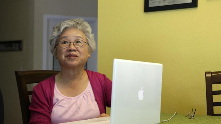 FILE - This Aug. 7, 2013 file photo shows Myunghee Bae, the mother of Kenneth Bae, at her computer in her home in Lynnwood, Wash. The gallery over the House of Representatives is filling up for President Barack Obama's State of the Union address. Democratic congressmen Rick Larsen of Washington and Charles Rangel of New York announced Tuesday they will host Myunghee Bae. (AP Photo/Ted S. Warren, File)