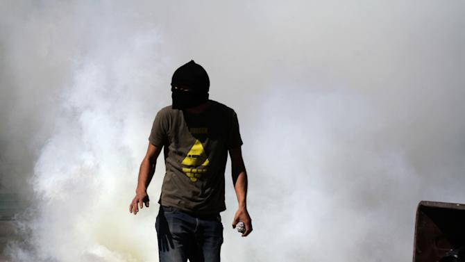 A Bahraini anti-government protester reacts to tear gas fired by riot police during clashes in Daih, Bahrain, on Thursday, Feb. 14, 2013, the second anniversary of the start of a pro-democracy uprising in the Gulf island kingdom. Protests began at daybreak in opposition areas nationwide as protesters attempted to return to the well-barricaded main site of the uprising. (AP Photo/Hasan Jamali)