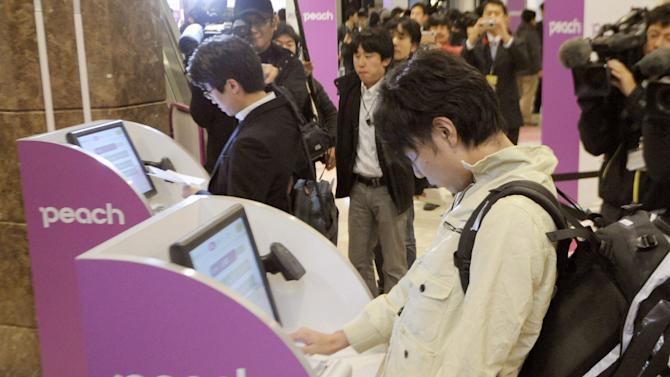 In this March 1, 2012 photo, passengers use self-service check-in kiosks to board the first flight by Peach Aviation at Kansai Airport in Osaka, western Japan. Japan has a reputation for loving expensive things like overpriced real estate, gourmet melons and luxury brands. But the nation is finally discovering the joy of flying cheap, with the arrival this year of three low-cost carriers. The takeoff of AirAsia Japan, Peach Aviation and Jetstar Japan could change lifestyles. (AP Photo/Kyodo News) JAPAN OUT, MANDATORY CREDIT, NO LICENSING IN CHINA, FRANCE, HONG KONG, JAPAN AND SOUTH KOREA