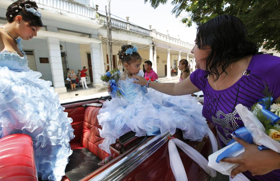 In this Friday April 20, 2012 a mother adjusts her younger daughter's necklace as the girl's sister steps into a rented 1950's era Chevrolet for a parade celebrating the older daughter's quinceanera, a girl's 15th birthday celebration, in Bayamo, Cuba.  (AP Photo/Kathy Willens)