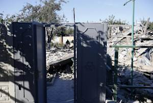 A woman observes damage at a destroyed home after shelling…