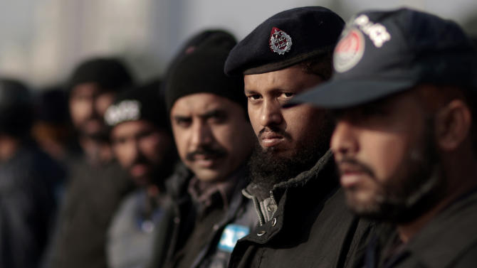 Pakistani policemen stand guard near the Parliament in preparation for a march led by cleric Tahir-ul-Qadri that is expected to arrive in Islamabad later in the day, in Islamabad, Pakistan, Monday, Jan. 14, 2013. Thousands of supporters of a fiery cleric who has been calling for election reforms were descending Monday on the Pakistani capital, where authorities have put up barricades and sent riot police into the streets in preparation. (AP Photo/Muhammed Muheisen)