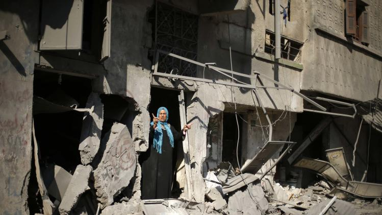 A Palestinian woman reacts outside her badly damaged house in Beit Hanoun town