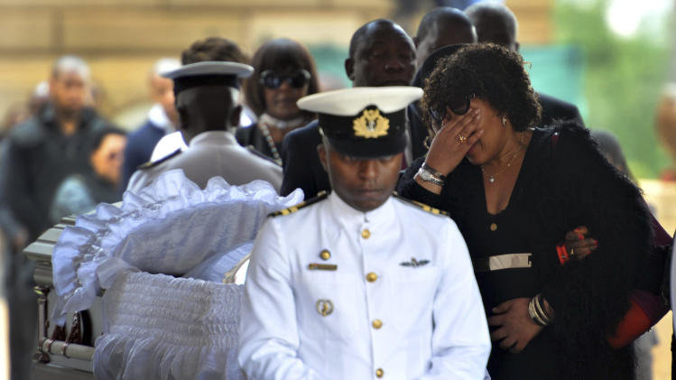 GCIS handout of Zenani Dlamini, daughter of former South African President Nelson Mandela, covering her eyes as she pays her respects at his coffin in Pretoria