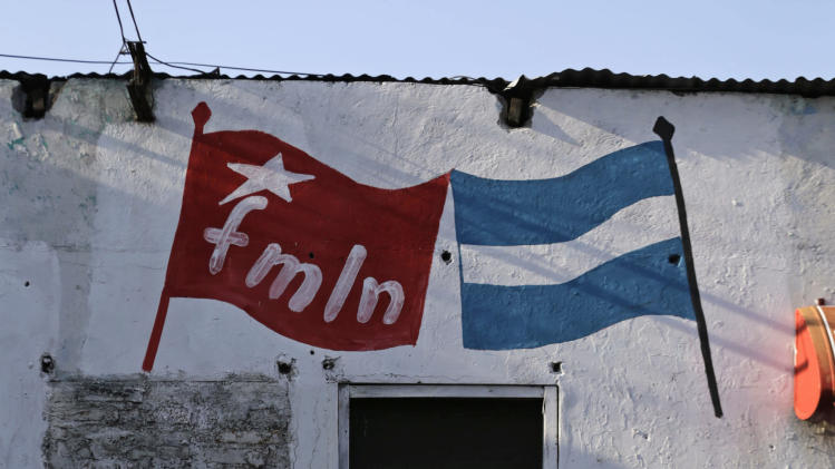 A pedestrian walks past a wall painted with the letters FMLN in San Salvador