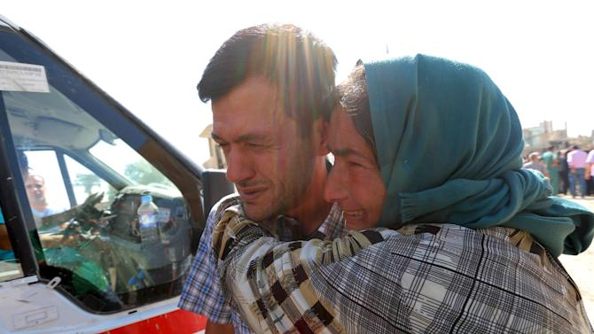 Abdullah Kurdi mourns with his relative during the funeral of his toddlers at the Syrian border town of Kobani