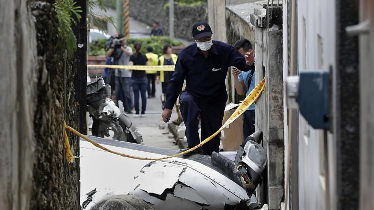Rescue personnel survey the wreckage of a TransAsia Airways turboprop plane that crashed on Penghu island