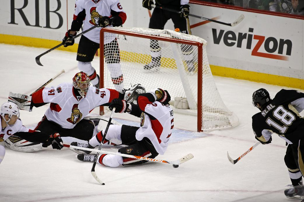 Pittsburgh Penguins' James Neal (18) gets the game-winning goal past Ottawa Senators goalie Craig Anderson (41), Marc Methot (3), and Jason Spezza (19), left, in overtime of an NHL hockey game in Pittsburgh, Monday, Feb. 3, 2014. The Penguins won 2-1