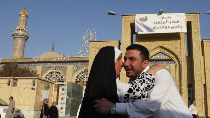 Iraqi Sunni Muslims exchange greetings after Eid prayers outside Abu Hanifa mosque at the first day of Eid al-Fitr prayers in the Azamiyah area of north Baghdad, Iraq, Sunday, Aug. 19, 2012. The three-day Eid al-Fitr holiday marks the end of the holy fasting month of Ramadan. (AP Photo/Karim Kadim)