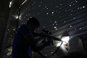 A Free Syrian Army fighter points his weapon as he tries to locate forces loyal to Syria's President Assad in Aleppo