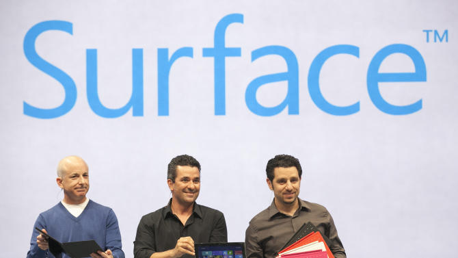 """Microsoft Surface design team members, from left, Steven Sinofsky, Mike Angiulo, and Panos Panay demonstrate """"Surface"""", a new tablet computer at Hollywood's Milk Studios in Los Angeles Monday, June 18, 2012. The 9.3 millimeter thick tablet comes with a kickstand to hold it upright and keyboard that is part of the device's cover. It weighs under 1.5 pounds. (AP Photo/Damian Dovarganes)"""
