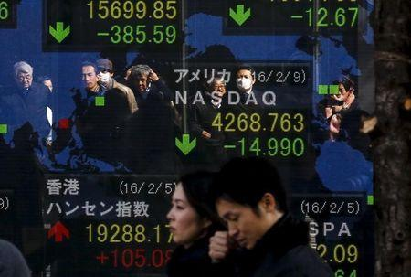People are reflected in a display showing market indices outside a brokerage in Tokyo