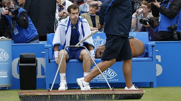 Britain's Andy Murray waits while the court is dried during a series of rain delays interrupting his men's singles tennis match against France's Nicolas Mahut at the Aegon Championships