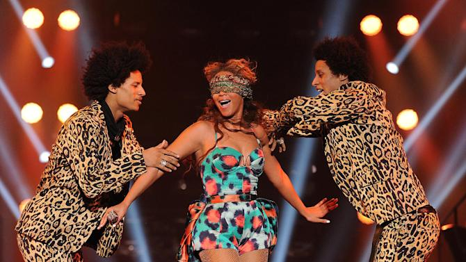"""Singer Beyonce performs the song """"Grown Woman"""" with dancers """"Les Twins"""" on her """"Mrs. Carter Show World Tour 2013"""", on Wednesday, April 24, 2013 at the Palais Omni Sport Bercy in Paris, France. Beyonce is wearing a custom printed romper with bustle by designer Kenzo. (Photo by Frank Micelotta/Invision for Parkwood Entertainment/AP Images."""