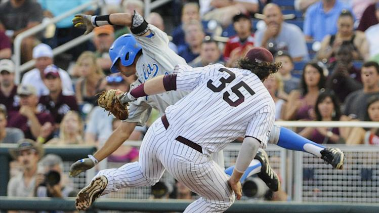 Mississippi State first baseman Wes Rea (35) and UCLA's Brian Carroll, rear, are sent spinning after they collide at first base in the fourth inning of Game 1 of the NCAA College World Series best-of-three finals, Monday, June 24, 2013, in Omaha, Neb. Carroll safe on the play. (AP Photo/Eric Francis)