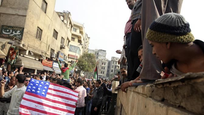 "Protesters chant slogans and carry a desecrated representation of an American flag during demonstrations against the Israeli invasion of Gaza, while marching through the streets towards Tahrir square after Friday prayers in Cairo, Egypt, Friday, Nov.16, 2012. In his Friday sermon at Al-Azhar mosque, influential cleric Sheikh Yusuf al-Qaradawi, not shown, said the Islamic world would not be silent in the face of Israel's military operation in Gaza. Arabic writing reads, ""death to Israel and death to America."" (AP Photo/Thomas Hartwell)"