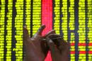An investor makes a note on his hand at a stock exchange market in Kunming