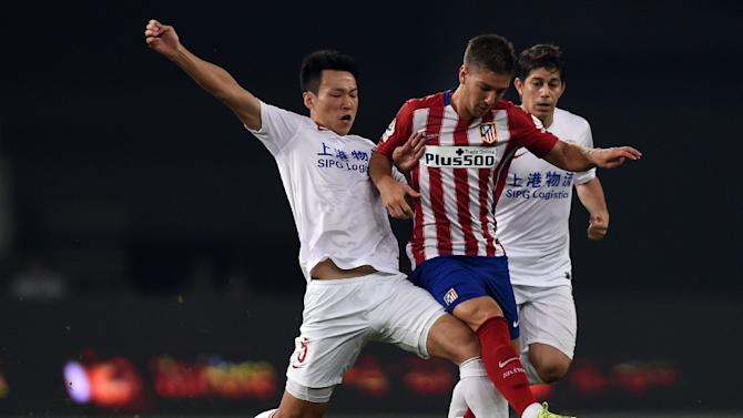 Atletico Madrid's Argentina forward Luciano Vietto (centre) is challenged by Shanghai's midfielder Jiajie Wang (left) and Argentinian forward Dario Conca during a friendly match in Shanghai on August 4, 2015