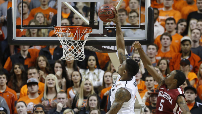 Oklahoma State guard Le'Bryan Nash (2) goes up for a dunk in front of Oklahoma guard Je'lon Hornbeak (5), guard Cameron Clark (21) and forward Romero Osby (24) with 53 seconds left in overtime of an NCAA college basketball game in Stillwater, Okla., Saturday, Feb. 16, 2013. Oklahoma State won 84-79. (AP Photo/Sue Ogrocki)