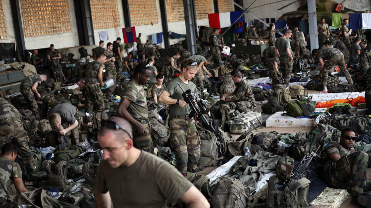 French troops gather in a hangar at Bamako's airport Tuesday 15 Jan. 2013.  French forces led an all-night aerial bombing campaign Tuesday to wrest control of a small Malian town from armed Islamist extremists who seized the area, including its strategic military camp. A a convoy of 40 to 50 trucks carrying French troops crossed into Mali from Ivory Coast as France prepares for a possible land assault. Several thousand soldiers from the nations neighboring Mali are also expected to begin arriving in coming days. (AP Photo/Jerome Delay)