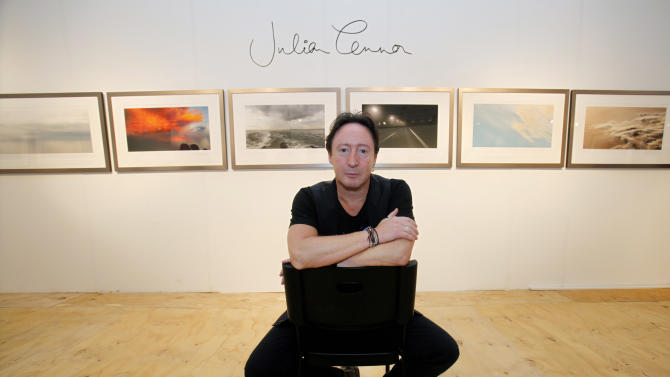 """Julian Lennon, son of the late Beatles legend John Lennon, poses in front of some of the photographs he is displaying in a show titled """"Alone"""" at the Overture Art Fair, Monday, Dec. 3, 2012 in Miami. Art Basel Miami Beach and about two dozen other independent art fairs open Thursday. Tens of thousands of people are expected through Sunday at the fairs throughout Miami and South Beach. Lennon also exhibited his photography during the 2010 art fairs, and he was looking forward to enjoying Miami's social scene. """"You get every kind of character and every kind of style,"""" he said. """"I just hope that doesn't detract from the actual work of the artists who've come here."""" (AP Photo/Wilfredo Lee)"""