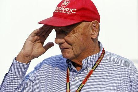 Austrian Formula One legend Lauda salutes as he walks in the paddock ahead of the Singapore F1 Grand Prix at the Marina Bay street circuit in Singapore