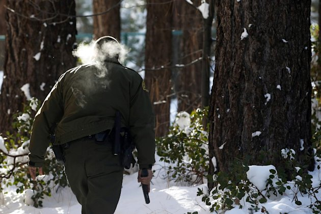 San Bernardino County Sheriff's officer Bernabe Ortiz holds a pistol as he searches a home for former Los Angeles police officer Christopher Dorner in Big Bear Lake, Calif, Sunday, Feb. 10, 2013. The