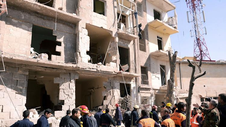 "This photo provided by the Syrian official news agency SANA shows Syrian rescue teams investigating the scene after an explosion in a residential neighborhood in Aleppo, Syria, Sunday, March 18, 2012. The state news agency said the explosion was a ""terrorist bombing."" The report by SANA gave no information on casualties in what appeared to be the second attack in two days on cities where President Bashar Assad's regime enjoys strong support. (AP Photo/SANA)"