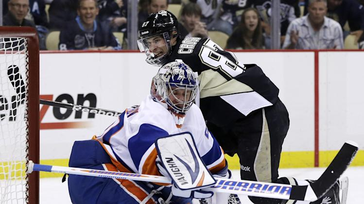 Pittsburgh Penguins' Sidney Crosby (87) gets the puck past New York Islanders goalie Evgeni Nabokov (20) for a goal in the second period of Game 5 of an NHL hockey Stanley Cup first-round playoff series, Thursday, May 9, 2013, in Pittsburgh. (AP Photo/Gene J. Puskar)
