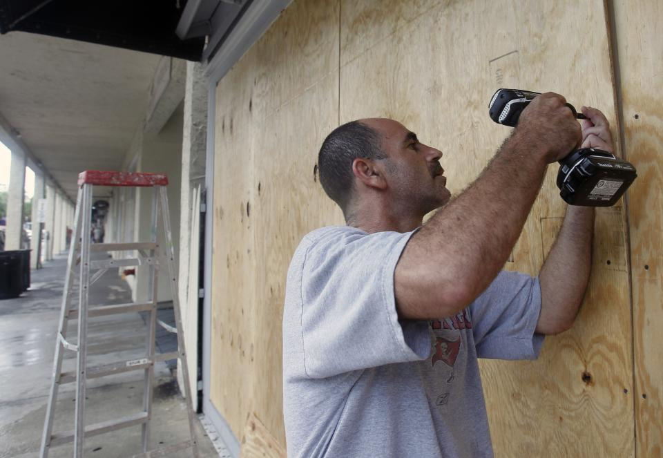 Oren Eshel boards a storefront on Duval Street in Key West, Fla., Saturday, Aug. 25, 2012 in preparation for Tropical Storm Isaac, Saturday, Aug. 25, 2012. Isaac's winds are expected to be felt in the Florida Keys by sunrise Sunday morning. (AP Photo/Alan Diaz)