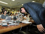 Yasuhiro Sato, president of Mizuho Financial Group, bows his head at a press conference in Tokyo on October 8, 2013 after Mizuho was told off by regulators for lending money to gangsters