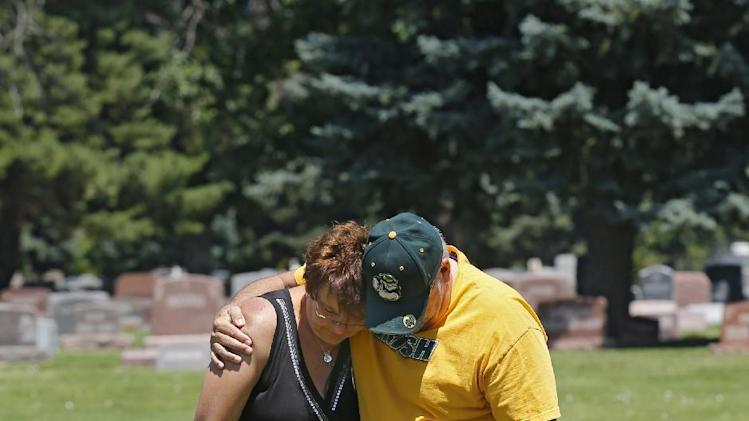 Tom Sullivan and his wife Terry visit the grave site of their son Alex Sullivan on Thursday, July 18, 2013, in Wheat Ridge, Colo. Alex was killed along with 11 others in the Aurora theater shooting last July on his 27th birthday. Saturday is the anniversary of the shooting. (AP Photo/Ed Andrieski)