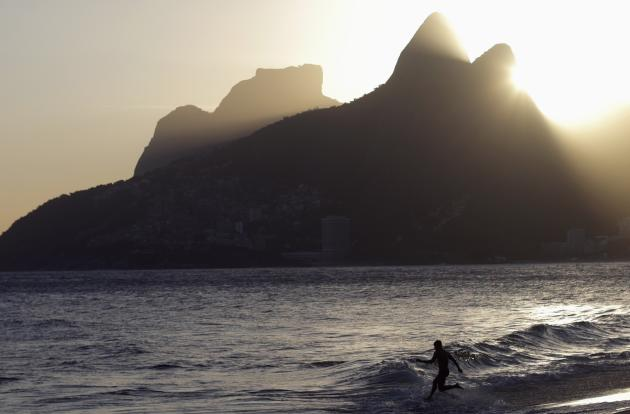A man jumps into the water in Arpoador beach in Rio de Janeiro