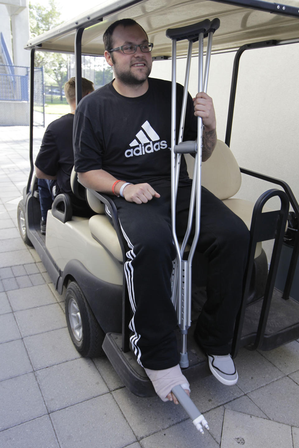 New York Yankees relief pitcher Joba Chamberlain gets a ride on a golf cart after speaking at a news conference in Tampa, Fla., Tuesday, March 27, 2012. Chamberlain injured his right ankle while bouncing on a trampoline during play with his son. (AP Photo/Kathy Willens)