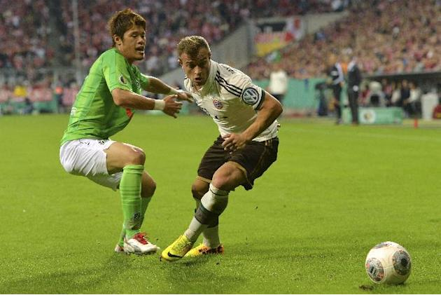 Munich's Xherdan Shaqiri of Switzerland, right, challenges for the ball with Hannover's Hiroki Sakai of Japan during the German soccer cup second round match between FC Bayern Munich and Hannover 96 ,
