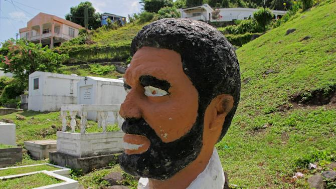 This picture taken Sunday, June 3, 2012, shows a bust of Grenada's former Prime Minister Maurice Bishop standing in a corner of a sprawling hillside cemetery where forensic experts believe the executed leader's body was buried in an unmarked grave in 1983 in St. George's, Grenada. A haunting Cold War mystery is getting a fresh look on the Caribbean island of Grenada, where the body of the Marxist prime minister is still missing nearly 30 years after he was executed during a bloody coup that sparked a U.S. invasion. (AP Photo/David McFadden)