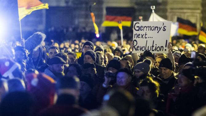 A woman holds a sign during a demonstration organised by anti-immigration group PEGIDA in Dresden