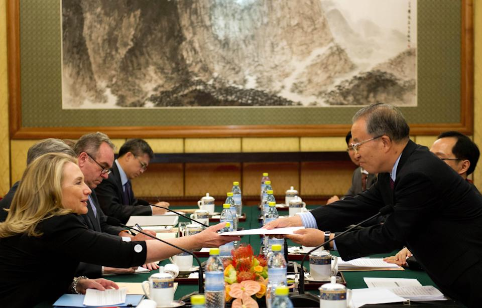Chinese State Councilor Dai Bingguo, right,  hands a letter to U.S. Secretary of State Hillary Rodham Clinton, left,  during a bilateral meeting at the Diaoyutai State Guesthouse in Beijing, China, on Wednesday, Sept. 5, 2012. (AP Photo/Jim Watson, Pool)