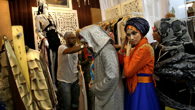 In this Thursday, May 30, 2013 photo, Indonesian Muslim women try on dresses during Islamic Fashion Fair in Jakarta, Indonesia. Indonesia is the world's most populous Muslim country, but most people follow a moderate form of the religion. Many women wear bright and creative headscarves along with brand-name jeans and long-sleeved fitted shirts. (AP Photo/Dita Alangkara)