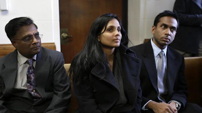 Annie Dookhan, center, sits between two unidentified men in Suffolk Superior Court moments before her arraignment in Boston, Thursday, Dec. 20, 2012. Dookhan, the former chemist at the center of a U.S. drug testing scandal, pleaded not guilty to charges including perjury and tampering with evidence. (AP Photo/Steven Senne, Pool)