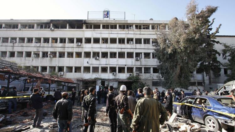 People stand at the site of a suicide bombing in Damascus, Syria, Friday, Dec. 23, 2011. A Syrian military official says the death toll from twin suicide car bombings in Damascus is now more dozens. The military official says more than a hundred people were wounded in the explosions targeting security and intelligence headquarters in the Syrian capital. (AP Photo/Muzaffar Salman)