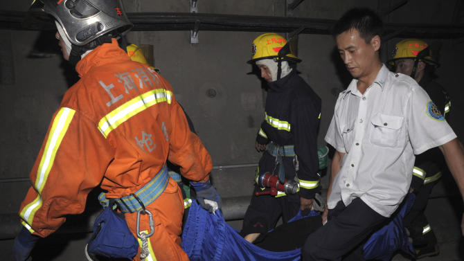Rescue workers carry an injured passenger in the subway tunnel from a train involved in a collision in Shanghai on Tuesday Sept. 27, 2011.   A Shanghai subway train rear-ended another Tuesday, injuring more than 40 people in the latest trouble for the rapidly expanded transportation system in China's commercial center. (AP Photo) CHINA OUT