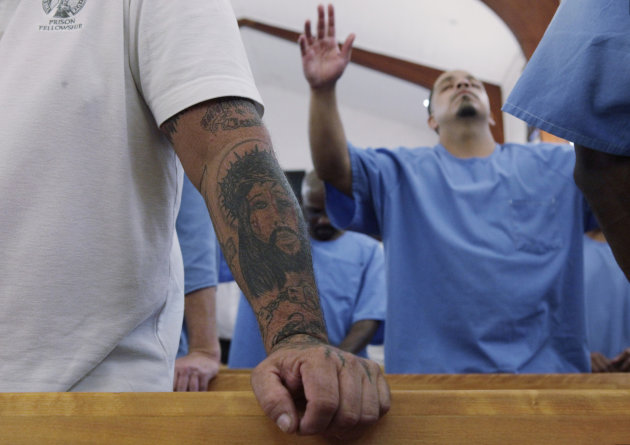 In this photo taken Thursday, Aug. 9, 2012, former inmate Owen Daniels' tattooed arm is seen at left, as he leads a college-level seminary course held at the California Rehabilitative Center in Norco, Calif. The program, called The Urban Ministry Institute, TUMI, started as an experiment in Norco's prison four years ago and is now expanding to 18 California prisons and nearly 900 inmates, including women, thanks to a $2.1 million gift from a wealthy Malibu real estate entrepreneur. The program aims to transform inmates into church leaders, pastors, teachers and evangelists. The TUMI Curriculum is divided into 16 eight-week courses covering biblical studies, theology and ethics, Christian ministry and urban mission. (AP Photo/Damian Dovarganes)