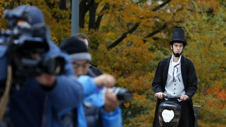 "As members of the media, left, wait, Christopher Brady, dressed as Abraham Lincoln, arrives on a Segway at the launching ceremony of the Lincoln Movie Trail at the State Capitol in Richmond, Va. Thursday, Nov. 15, 2012. With Steven Spielberg's ""Lincoln"" set for national release Friday, Virginia tourism officials are inviting fans of history and film to tour the locations where the epic movie was made. (AP Photo/Richmond Times-Dispatch, Bob Brown)"