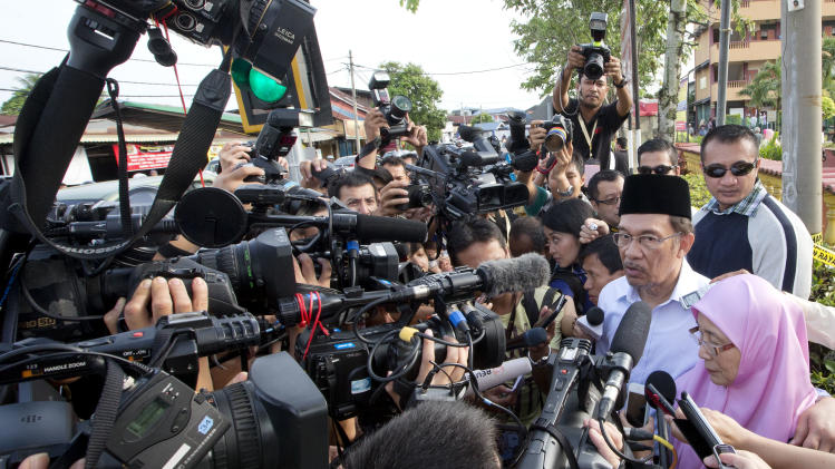 Malaysian opposition leader Anwar Ibrahim and his wife Wan Azizah are surrounded by media after voting at a polling station at Penanti in Penang state in northern Malaysia, Sunday, May 5, 2013. Malaysians have begun voting in emotionally charged national elections that could see the long-ruling coalition ousted after nearly 56 years in power.   (AP Photo/Mark Baker)