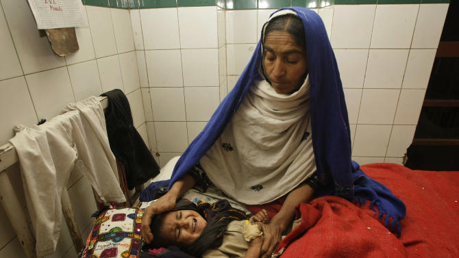 A Pakistani mother attends to her child suffering from measles, at a local hospital in Sukkar, Pakistan, Tuesday, Jan. 1, 2013. Measles cases surged in Pakistan in 2012 with hundreds of children dying of the disease, the World Health Organization said Tuesday. Pakistani officials in recent days say they have launched an immunization campaign to reach children in the worst-hit areas. (AP Photo/Fareed Khan)