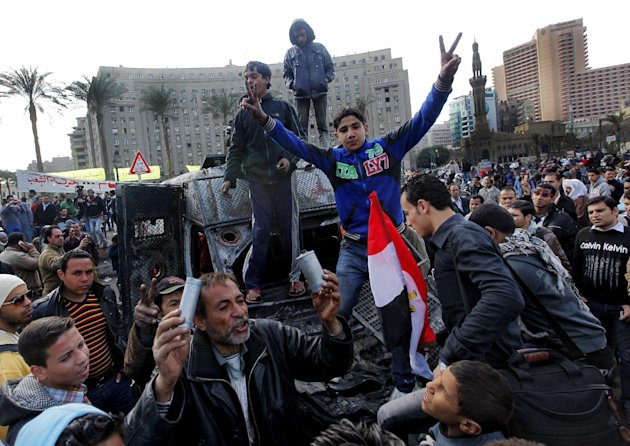 Egyptian protesters celebrate the capture of a state security armored vehicle that demonstrators commandeered during clashes with security forces and brought to Tahrir Square in Cairo, Egypt, Tuesday,