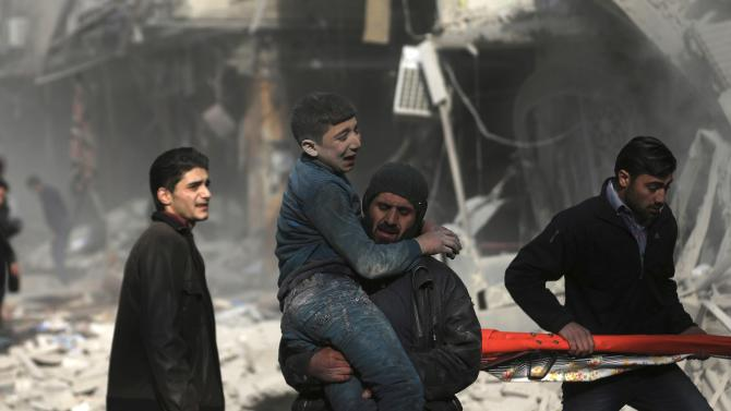 A man carries an injured civilian at a site hit by what activists said was an air strike by forces of Syria's President Bashar al-Assad in the Duma neighbourhood of Damascus